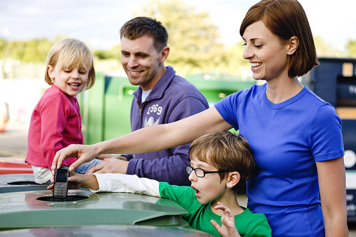 Family putting old phone in recycle bin